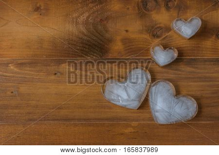 Heart shaped ice on brown wooden background