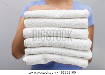 Maid holding a stack of white fresh towels stock photo