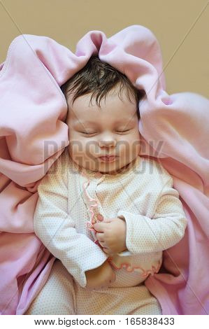 new born baby is lying in pajamas, sleeping baby, eyes are closed, on blanket