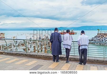 Three young Orthodox Hasid friends in traditional skullcaps and tallits stand on embankment of the Sea of Galilee and enjoy the view Tiberias Israel.