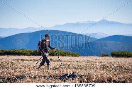 Male Backpacker Is Walking With Trekking Sticks