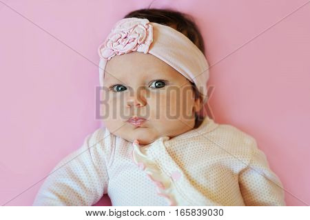 Portrait of a cute little girl with a crown on the head lying on pink background