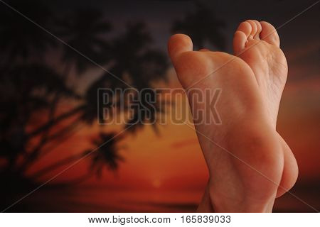 Girls feet on the background of palm trees and sunset - relax