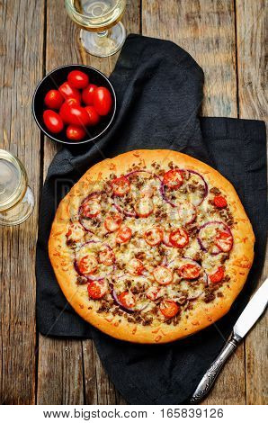 Minced meat tomato red onion pizza on a wood background.