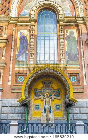 The painted Crucifix on the wall of Cathedral on Spilled Blood decorated with fretwork gilt mosaics and carved patterns St Petersburg Russia.