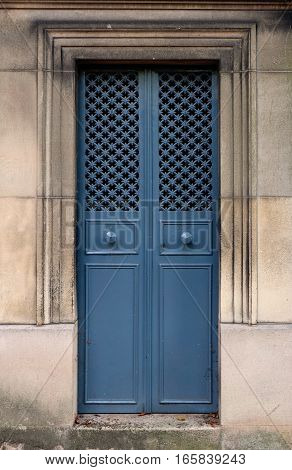 Closed steel double door with door knobs and hole pattern. The iron is blue colored, the doorframe is rectangle and ornate with chiseled lines. The texture consists of small crosses connected by metal bars.