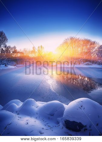Winter landscape by a frozen river. Mirror reflection at sunset