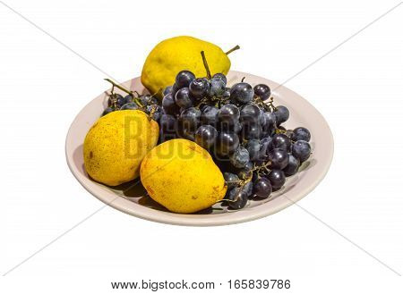 Yellow pear and grapes on the plate.