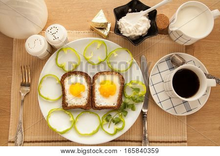 Healthy breakfast with toasted bread and eggs with cup of tea and milk. Fast snack with yolk and coffee.