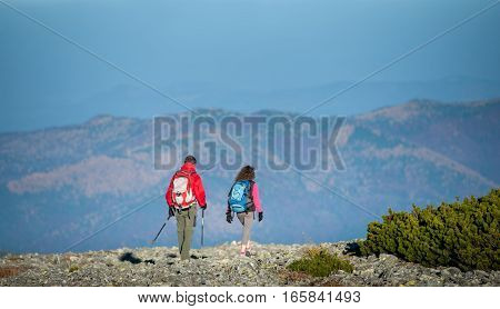 Young Couple Hikers With Backpacks Walking On Rocky Mountain Plato