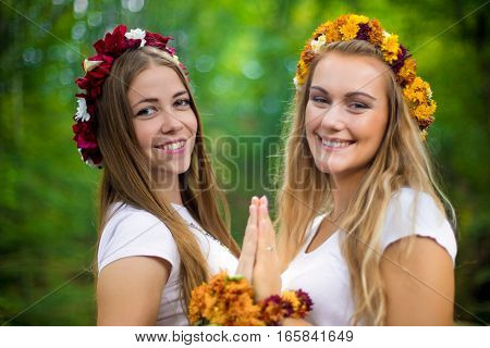 Two girls in national slavic costumes at in a beautiful green forest