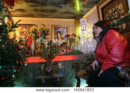 Bucharest Romania December 25 2009: A gypsy woman is praying in the family's chapel decorated in a kitsch manner in a cemetery in Bucharest.