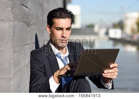 Businessman Using A Laptop Computer Sitting In The Street