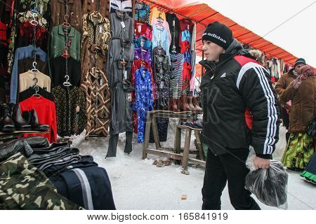 Calugareni Romania December 20 2009: A young man is looking at different products in the animal market in Calugareni. Before Christmas animal breeders are selling and sacrificing their animals in animal markets and vendors are selling different products.