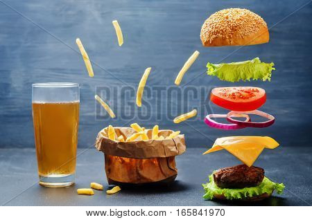 Flying burger with flying French fries and beer on a dark background.