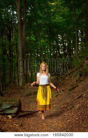 Beautiful blonde girl with long hair in national dress posing in dark green forest