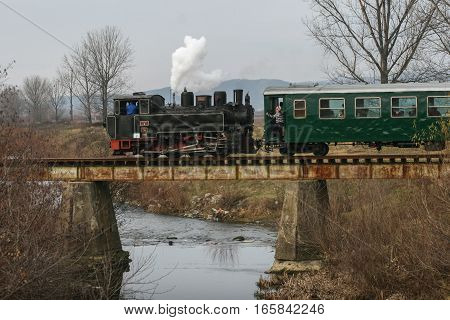Brad Romania December12 2009: An old steamed cog train is crossing a bridge in Brad on winter holydays.