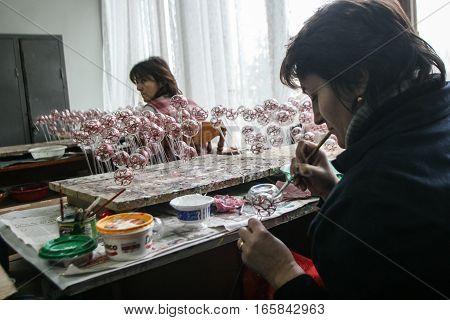 Curtea de Arges Romania December 14 2009: A woman paints with a brush Christmas balls in Argocoms Glass factory in Curtea de Arges.