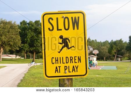 Slow down sign for children at side of road