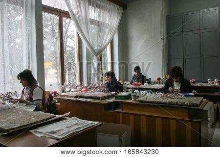 Curtea de Arges Romania December 14 2009: Women are decorating Christmas balls in Argocoms Glass factory in Curtea de Arges.