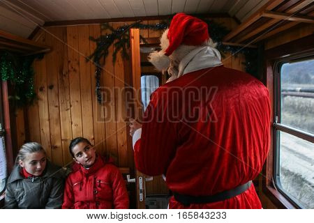 Brad Romania December12 2009: A man dressed in Santa Claus shares sweets to the tourists in an old steamed cog train in Brad on winter holydays.