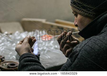 Curtea de Arges Romania December 14 2009: A man is manufacturing glass Christmas balls in Argocoms Glass factory in Curtea de Arges.