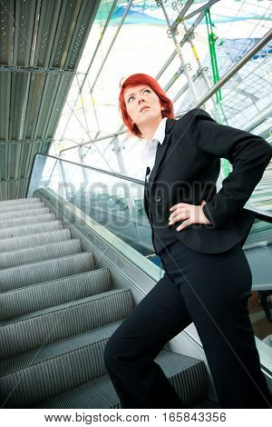 businesswoman going up an escalator, scaffolding visible in the background