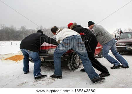 Calugareni Romania December 20 2009: Four men are pushing a car in an animal market in Calugareni. Before Christmas animal breeders are selling and sacrificing their animals in animal markets and vendors are selling different products.