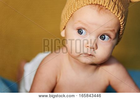 newborn baby with big eyes hat-knitting on a plain background.