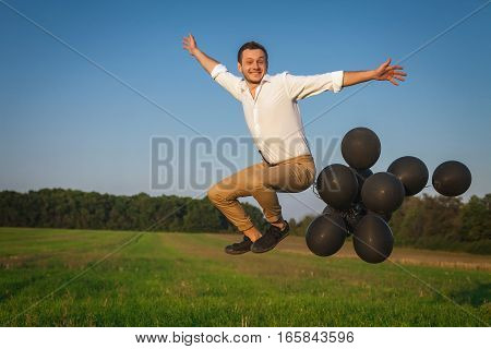 man in white shirt and brown pants jumping with black balloons arms outstretched to the sides