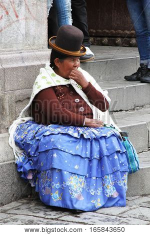 La Paz Bolivia - December 12 2016: Woman in traditional dress and bowler hat sits on step in La Paz Bolivia on December 12 2016