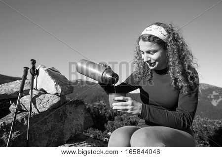 Girl Hiker Pouring Tea Out Of Thermos. Black And White