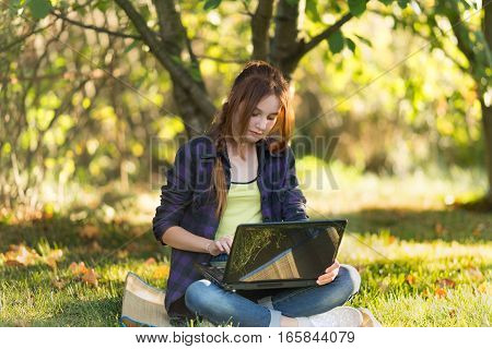 Girl in jeans sitting on the grass in the garden with the laptop