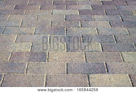 Street paved with gray tiles. Close-up view
