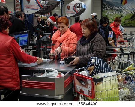 Bucharest Romania December 24 2015: Customers paying for shopping at a supermarket in Bucharest.