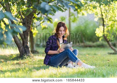 Girl in jeans sits on green grass in the garden with your tablet