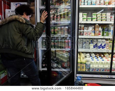 Bucharest Romania December 24 2015: A woman chooses beer from a freezer inside a supermarket in Bucharest.