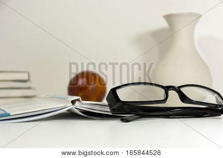 black-rimmed glasses sunglasses book orange vase pile of books lying on white Desk on white background