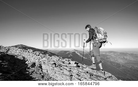Tourist Backpacker Walking On The Rocky Ridge Of The Mountain
