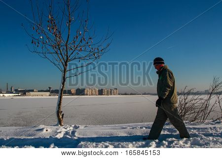 Bucharest Romania January 1 2015: A man walks on the edge of a lake in Bucharest during a cold winter day.