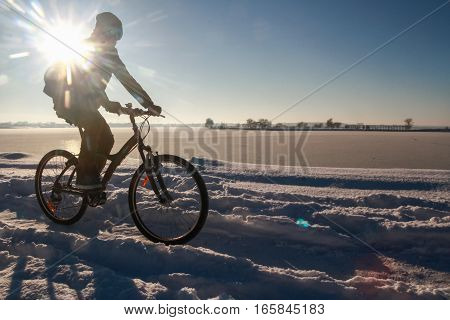 Bucharest Romania January 1 2015: A man rides his bike on the edge of a lake in Bucharest during a cold winter day.