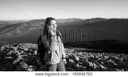 Portrait Of Woman Backpacker On Rocky Top Of The Mountain