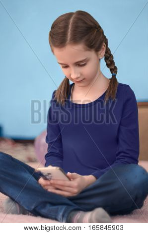Girl with braids sitting on bed using smartphone
