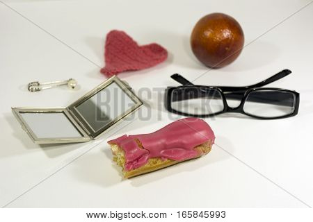cupcake éclair with pink icing glasses mirror safety pin with pearl orange pink heart female things lying on a white table