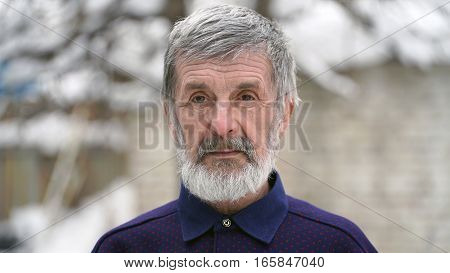 a portrait of an elderly man outdoors