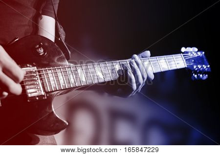 Guitar neck close-up on a concert of rock music in the hands of a musician