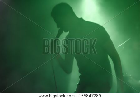 Blurred silhouette of a musician with a microphone during a concert in backlight on the stage in the smoke