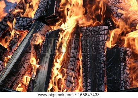 burning logs burned in the fire - background