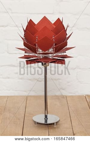 Front view of brown conceptual table lamp on wooden stand on white brick wall background