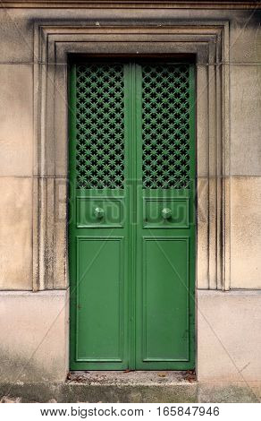 Green closed steel door - A rectangle double door with door knobs made of iron, ornate with a texture of small crosses.